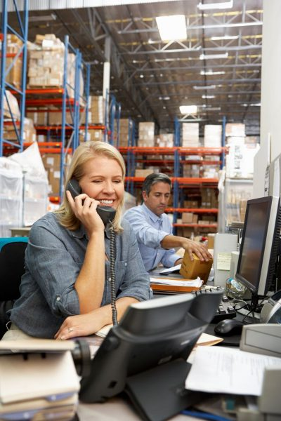 businesswoman-working-at-desk-in-warehouse-PK3QYHP